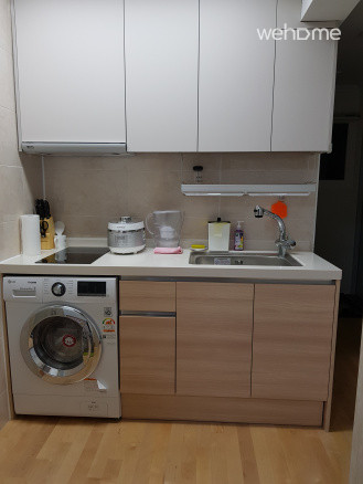 Kitchen with drum washer and dryer